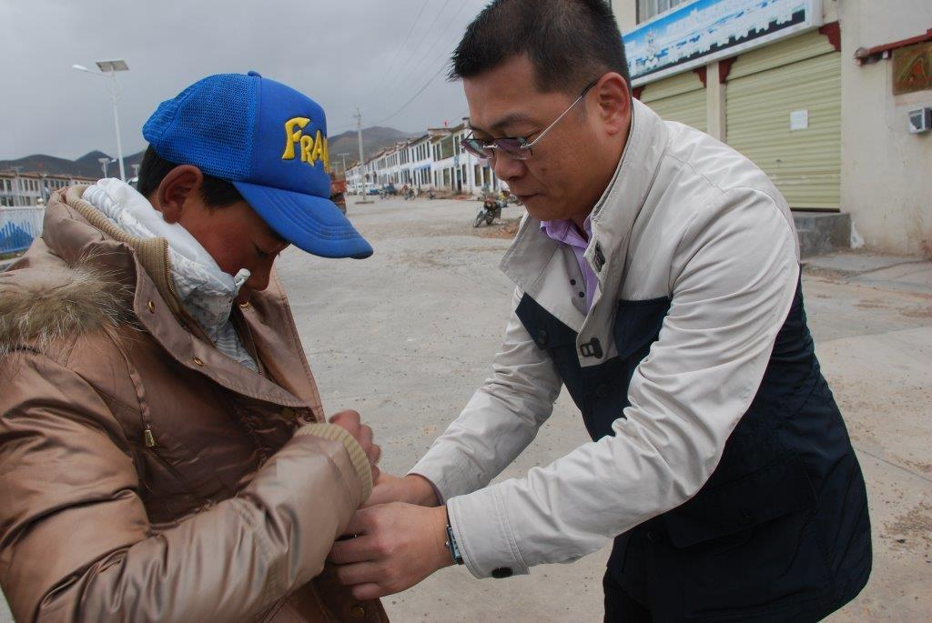 2015年7月,金利来集团副主席兼行政总裁曾智明在西藏为孩子穿上寒衣